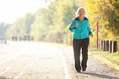 picture of 70-year-old  - 70 years old Senior Woman Jogging at the Pedestrian Walkway in the Bright Autumn Evening - JPG