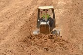 stock photo of bulldozer  - Small bulldozer moving dirt from a hillside in preperation for a new commerical construction development - JPG
