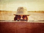 stock photo of old suitcase  - Hipster girl in hat and glasses looks out from vintage suitcase - JPG