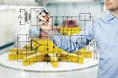 stock photo of interior sketch  - electrical engineer draws a diagram of a circuit - JPG