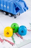 stock photo of garbage bin  - Colored trash bins and garbage truck toys on business background - JPG