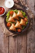 stock photo of samosa  - Indian samosa delicious pastry on a plate on a wooden table - JPG