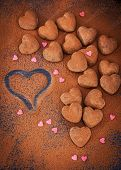 foto of truffle  - Heart shaped chocolate truffles on cocoa powdered table Valentine concept - JPG