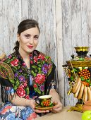 stock photo of bagel  - Beautiful brunette sitting at the samovar with bagels - JPG