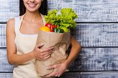 stock photo of apron  - Cropped image of beautiful young woman in apron holding paper shopping bag full of fresh vegetables and smiling while standing in front of wooden background - JPG