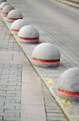image of paving stone  - Round stone road kerb with a red strip standing in a row and on a diagonal on a paving stone - JPG