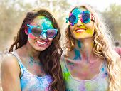 foto of holi  - Portrait of happy young girls on holi color festival - JPG