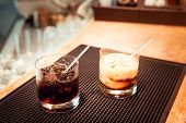 foto of marsala  - Black russian and white russian cocktails on the bar stand on rubber mat. Shallow DOF and marsala tonned ** Note: Visible grain at 100%, best at smaller sizes - JPG