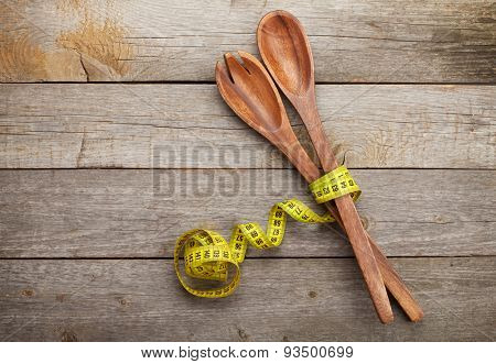 Measure tape with kitchen utensils. Diet food on wooden table with copy space