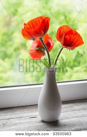 Red Poppies In A White Vase On A Light Wooden Background