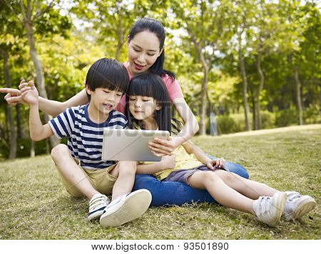 Asian Mother And Children Using Tablet Computer