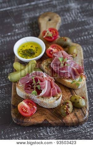 Toast With Ham, Olives And Cherry Tomatoes In Olive Board On A Light Wooden Background