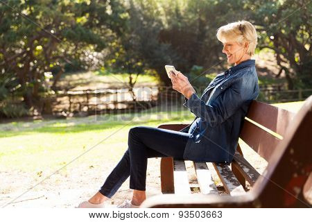 beautiful middle aged woman using smart phone outdoors