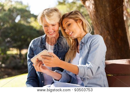 beautiful young daughter using smart phone with mid age mother outdoors