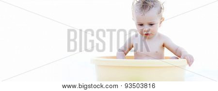 Cute White Baby Playing in a Yellow Bath Basin Alone, Isolated on White Background, Emphasizing Copy Space.