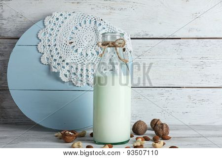 Milk in glassware and walnuts on wooden background