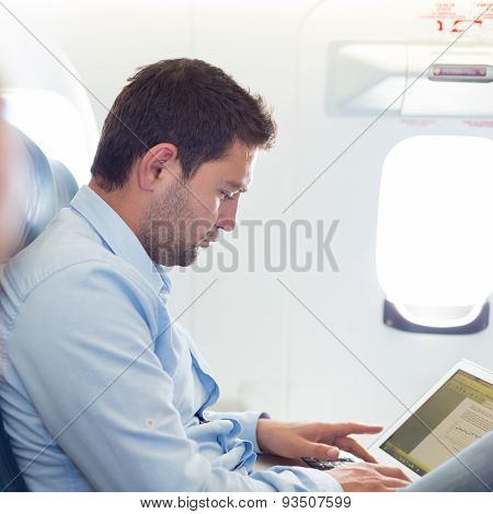 Businessman working with laptop on airplane.