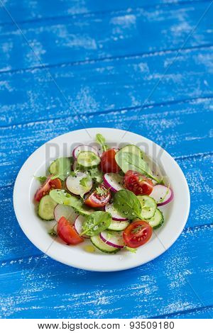 Fresh Salad With Cherry Tomatoes, Cucumber, Radish And Spinach On A White Plate On Blue Wooden Backg