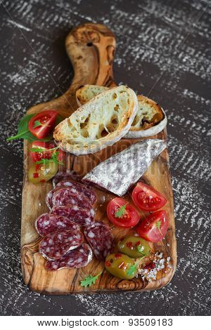 Italian Sausage, Ciabatta, Olives And Cherry Tomatoes In Olive Board On Dark Wooden Background