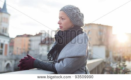 Thoughtful woman outdoors on cold winter day.