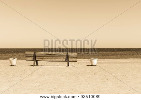 Wooden Sepia Bench On The Sandy Beach Seashore