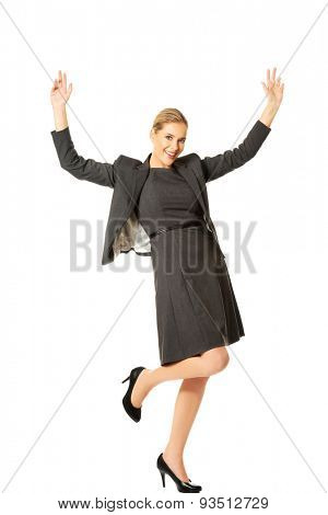 Smiling cheerful businesswoman with arms up