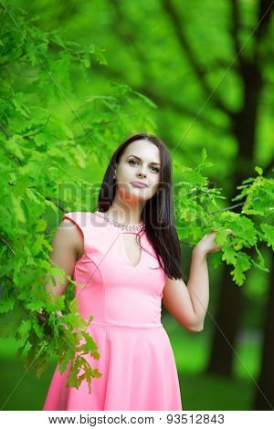 Young spring fashion woman. Trendy girl in the branches of the oak in the spring summer garden. Springtime or summertime. Lady in spring landscape background.