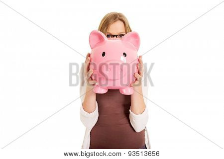 Happy teenage woman holding piggybank