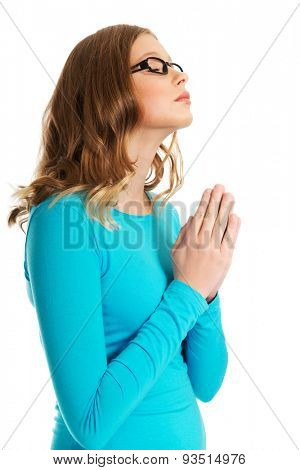 Teenage woman praying with clenched hands