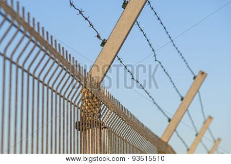 Security Post With Barbed Wire Fence Closeup