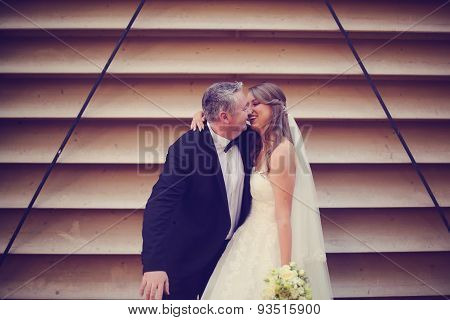 Bride And Groom Having Fun On A Striped Wall