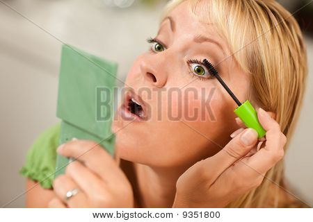 Mujer rubia aplicando su Mascara