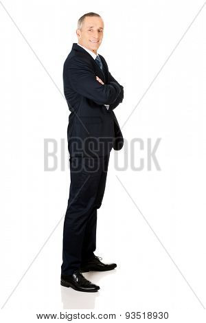 Full length side view businessman with folded arms.