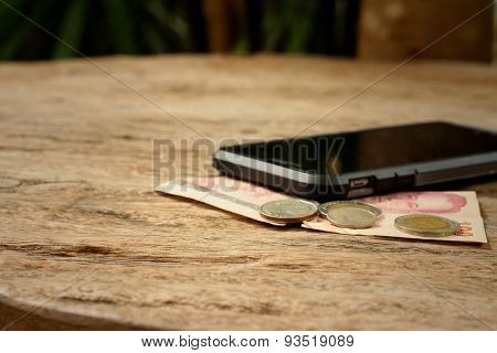 Smart Phone With Money Of Thai Bath On Wooden Background.