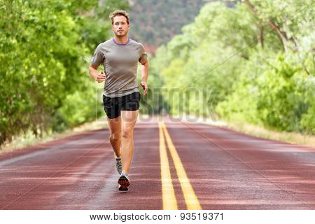 Sport and fitness runner man running on road training for marathon run doing high intensity interval