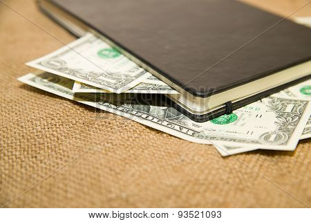 Notebook And Money On The Old Tissue