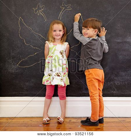 Two Little Kids In Front Of Blackboard With Angel Wings