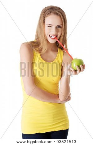 Attractive young woman in yellow top is drinking from and apple with a straw. Isolated on white.