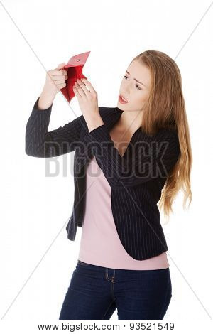 Young beautiful woman is looking into her empty wallet. Isolated on white.