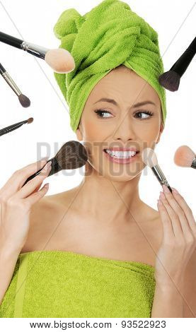 Beautiful scared woman has brushes around face.