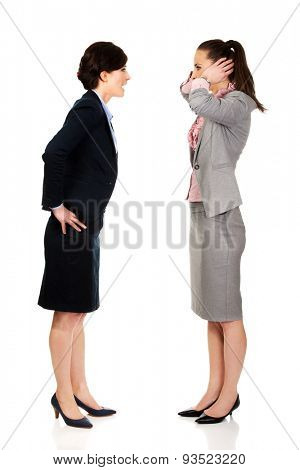 Businesswoman covering ears from her angry partner.