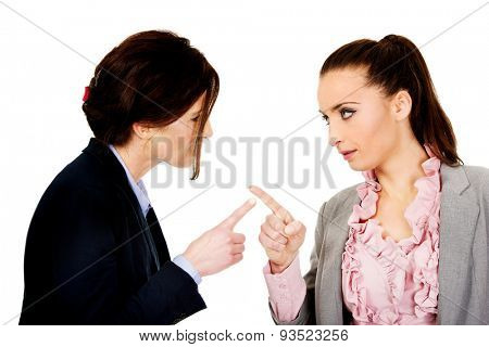 Two angry businesswomans pointing on each other.