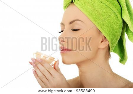 Beautiful woman smelling cream moisturizer.