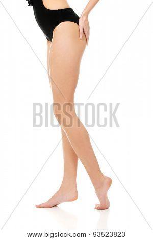 Beautiful slim woman's legs in black swimsuit.