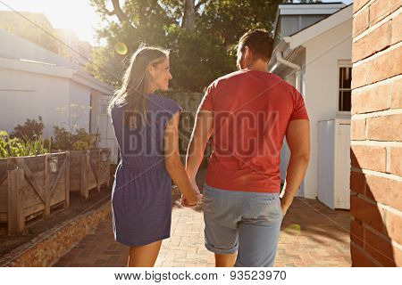 Young Couple Taking A Walk In Their Backyard