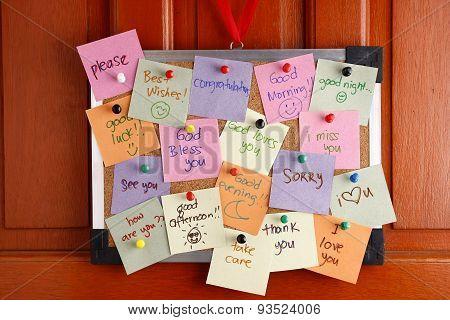 Cork board with messages on colorful papers and push pins hanging by a door