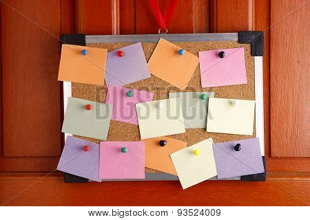Cork board with colorful papers and push pins hanging by a door