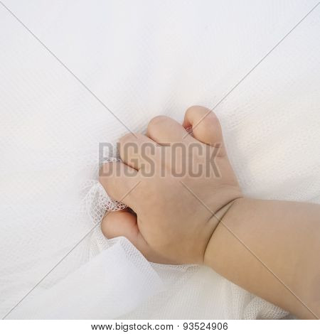 Baby hand on white fabric background