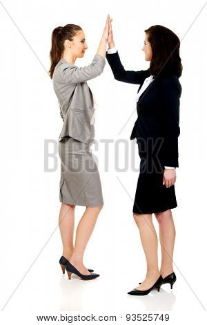 Two successful businesswoman giving a high five.