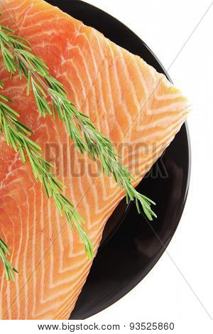 raw fresh uncooked salmon red fish fillet on black plate with rosemary twig isolated over white background